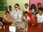 Ana Paula, os kits e as crianças em Domiciano (Sanderson Pereira/Photo Esporte)